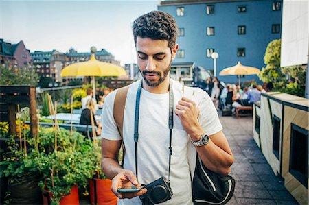 Male tourist using smart phone in city Stock Photo - Premium Royalty-Free, Code: 698-08393334