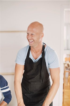 Happy man in apron looking away while standing in kitchen Stock Photo - Premium Royalty-Free, Code: 698-08393412
