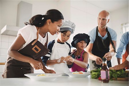 Family preparing Asian food at table in kitchen Stock Photo - Premium Royalty-Free, Code: 698-08393423