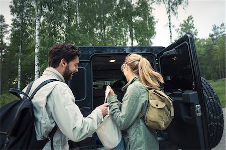 Side view of wonderlust couple unloading bag from jeep at countryside Stock Photo - Premium Royalty-Free, Code: 698-08393488