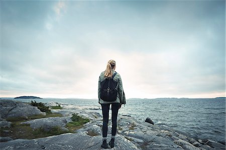friluftsliv - Rear view of woman standing on rock by sea against cloudy sky Stock Photo - Premium Royalty-Free, Code: 698-08393483