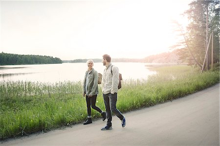 Full length of happy wonderlust couple walking on road by lake against clear sky Stock Photo - Premium Royalty-Free, Code: 698-08393496
