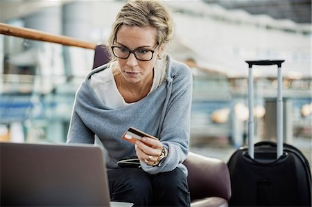 Businesswoman using credit card and laptop at airport lobby Stock Photo - Premium Royalty-Free, Code: 698-08434228