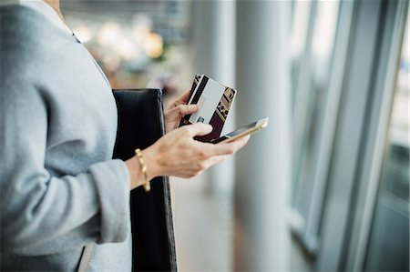 person on phone with credit card - Midsection of businesswoman using smart phone at airport Stock Photo - Premium Royalty-Free, Code: 698-08434244
