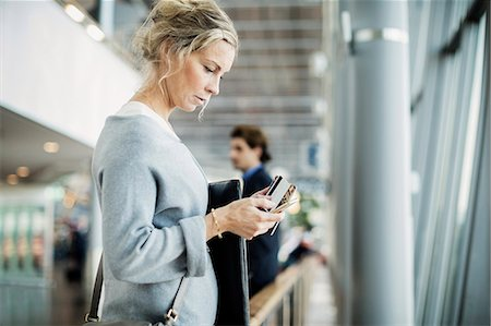 Side view of businesswoman using smart phone at airport Stock Photo - Premium Royalty-Free, Code: 698-08434245