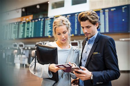 Business people using smart phone while looking at passport in airport Stock Photo - Premium Royalty-Free, Code: 698-08434262