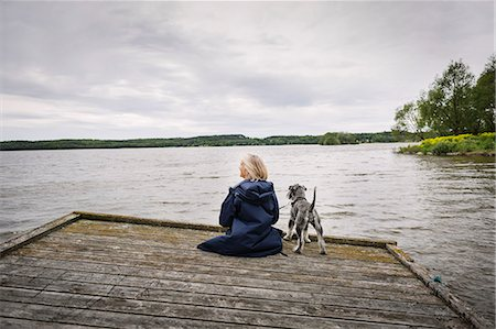 Rear view of senior woman and dog on pier at lake against cloudy sky Stock Photo - Premium Royalty-Free, Code: 698-08434343