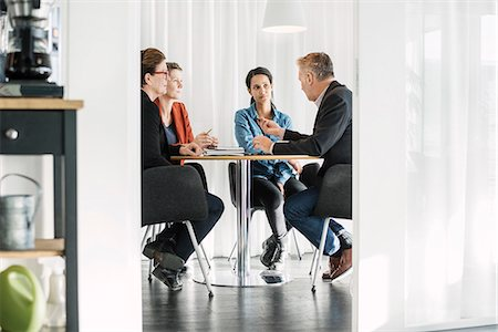 strategy - Businessman explaining business strategy to colleagues in meeting Stock Photo - Premium Royalty-Free, Code: 698-08434382