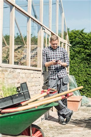 farm phone - Man using smart phone while leaning on greenhouse at community garden Stock Photo - Premium Royalty-Free, Code: 698-08434441