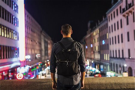 Rear view of man carrying backpack standing on bridge in city at night Stock Photo - Premium Royalty-Free, Code: 698-08434457