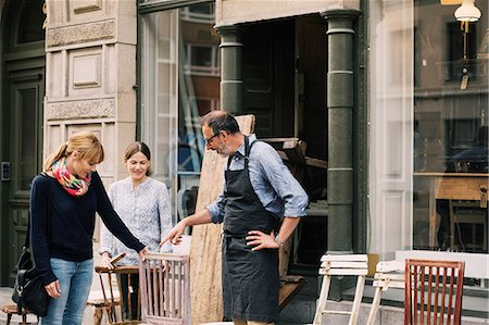 Smiling retailers assisting woman outside shop Stock Photo - Premium Royalty-Free, Code: 698-08434521