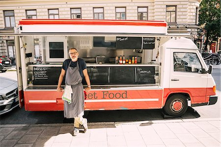stockholm - Full length of male chef standing against food truck at city street Stock Photo - Premium Royalty-Free, Code: 698-08434556