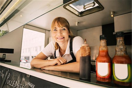 Portrait of happy female chef leaning on counter at food truck Stock Photo - Premium Royalty-Free, Code: 698-08434557