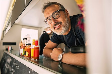 Portrait of happy male chef leaning on counter at food truck Stock Photo - Premium Royalty-Free, Code: 698-08434558
