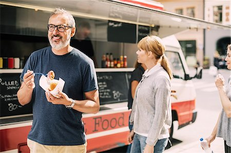 Mature man eating food while standing against truck at street Stock Photo - Premium Royalty-Free, Code: 698-08434552