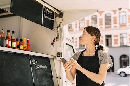 restaurant - Female chef using mobile phone while looking at menu on food truck Stock Photo - Premium Royalty-Free, Code: 698-08434561