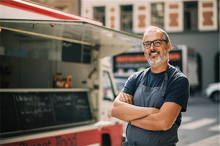 small business - Portrait of confident chef with arms crossed standing by food truck on street Stock Photo - Premium Royalty-Free, Code: 698-08434574