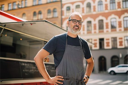 Portrait of confident chef standing by food truck on street in city Stock Photo - Premium Royalty-Free, Code: 698-08434573
