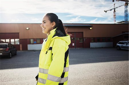 Side view of female auto repair student standing outside school Stock Photo - Premium Royalty-Free, Code: 698-08545066