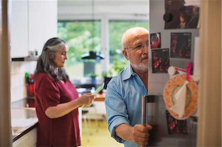 fridge - Senior man opening refrigerator while woman using digital tablet at home Stock Photo - Premium Royalty-Free, Code: 698-08545148