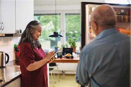fridge - Side view of senior woman using digital tablet while man standing at refrigerator Stock Photo - Premium Royalty-Free, Code: 698-08545149