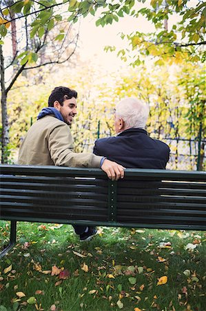 Rear view of caretaker looking at senior man while sitting on bench at park Stock Photo - Premium Royalty-Free, Code: 698-08545204