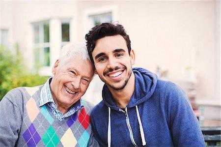 Portrait of happy senior man with caretaker sitting outdoors Stock Photo - Premium Royalty-Free, Code: 698-08545203
