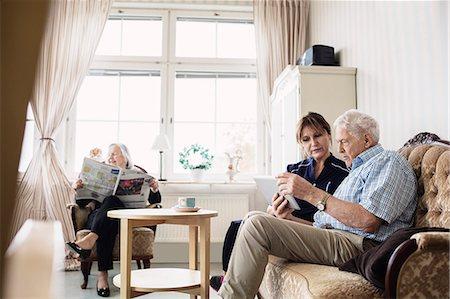 Senior man and caretaker using digital tablet while woman reading newspaper in nursing home Stock Photo - Premium Royalty-Free, Code: 698-08545216