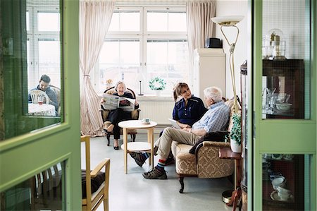 Caretakers with senior couple sitting in living room at nursing home Stock Photo - Premium Royalty-Free, Code: 698-08545217