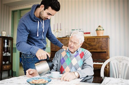 Caretaker serving coffee to senior man at nursing home Stock Photo - Premium Royalty-Free, Code: 698-08545248