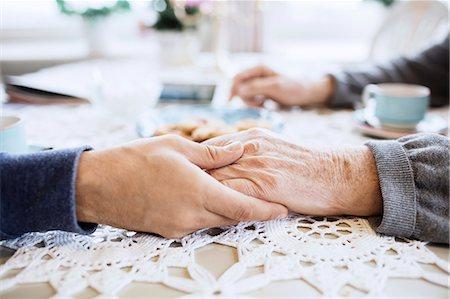 Cropped image of caretaker consoling senior man at dining table Stock Photo - Premium Royalty-Free, Code: 698-08545249