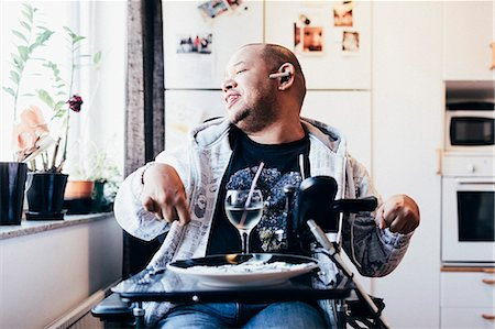 Happy disabled musician with drink sitting by window at recording studio Stock Photo - Premium Royalty-Free, Code: 698-08545309