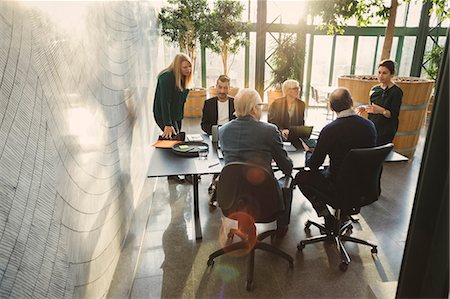 Businesswoman discussing with colleagues at table in creative office Stock Photo - Premium Royalty-Free, Code: 698-08545443