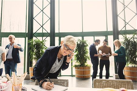 europe - Mature businesswoman on call while writing in notepad with colleagues in background at office Stock Photo - Premium Royalty-Free, Code: 698-08545462