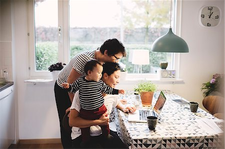 Lesbian couple with daughter looking in laptop at kitchen Stock Photo - Premium Royalty-Free, Code: 698-08545492