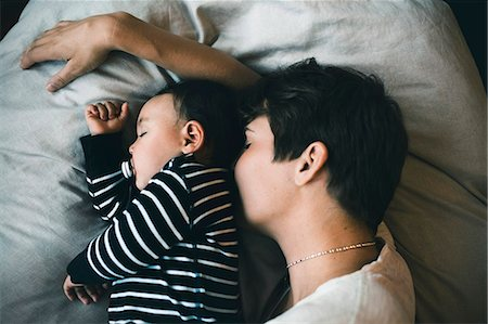 High angle view of mother and toddler sleeping on bed at home Stock Photo - Premium Royalty-Free, Code: 698-08545507
