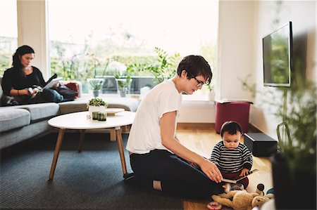 Mother and daughter playing with toys while woman using digital tablet at home Stock Photo - Premium Royalty-Free, Code: 698-08545516