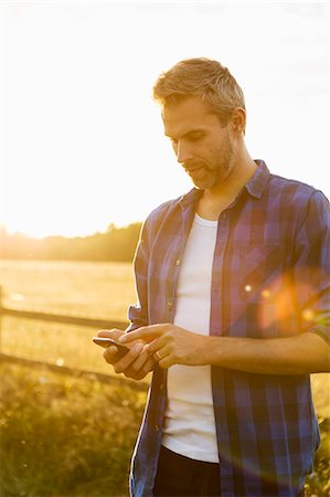 farm phone - Man using phone while standing on field against sky Stock Photo - Premium Royalty-Free, Code: 698-08549669