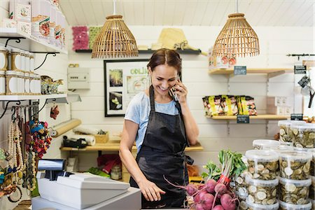 fresh - Happy woman talking on mobile phone while standing at counter in store Stock Photo - Premium Royalty-Free, Code: 698-08549740