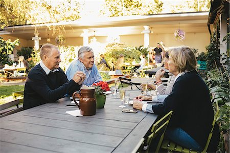 Happy senior couples discussing at outdoor restaurant Stock Photo - Premium Royalty-Free, Code: 698-08549824