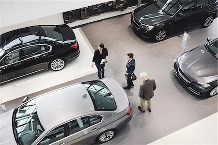 High angle view of saleswoman assisting customers at car showroom Stock Photo - Premium Royalty-Free, Code: 698-08549878