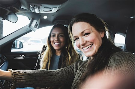 Portrait of smiling friends sitting in car at showroom Stock Photo - Premium Royalty-Free, Code: 698-08549885
