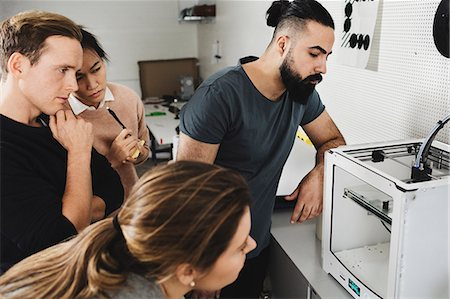 Creative start-up business team looking at 3D printer in workshop Stock Photo - Premium Royalty-Free, Code: 698-08549925