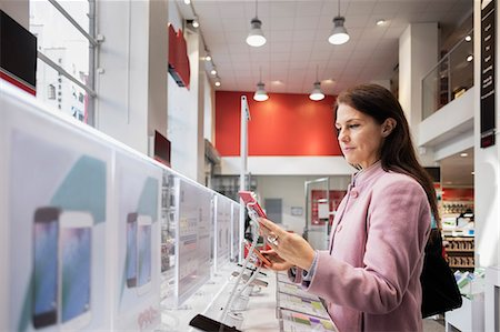 purchase - Side view of woman using smart phone in store Stock Photo - Premium Royalty-Free, Code: 698-08580234