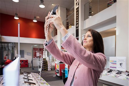 purchase - Smiling woman taking selfie in store Stock Photo - Premium Royalty-Free, Code: 698-08580233