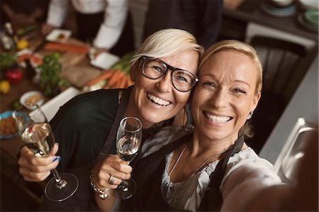 Cheerful mature women holding champagne flutes while taking selfie in kitchen Stock Photo - Premium Royalty-Free, Code: 698-08580247