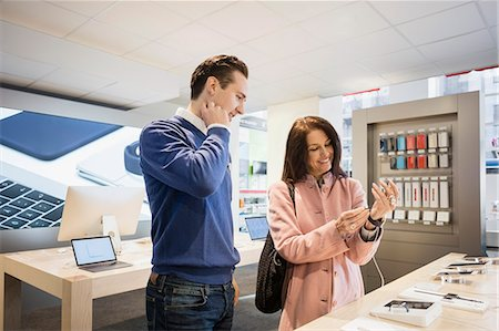 purchase - Happy female customer wearing smart watch while standing with salesman in store Stock Photo - Premium Royalty-Free, Code: 698-08580241