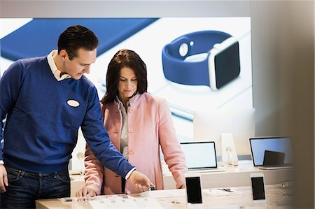 purchase - Salesman assisting customer in buying smart watch at store Stock Photo - Premium Royalty-Free, Code: 698-08580243