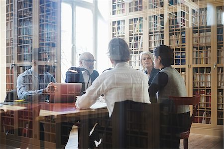 Lawyers sitting at table during meeting seen through glass in law library Stock Photo - Premium Royalty-Free, Code: 698-08580334