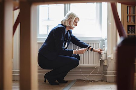 photograph - Senior woman crouching while charging mobile phone by radiator with furniture in foreground at library Stock Photo - Premium Royalty-Free, Code: 698-08580337